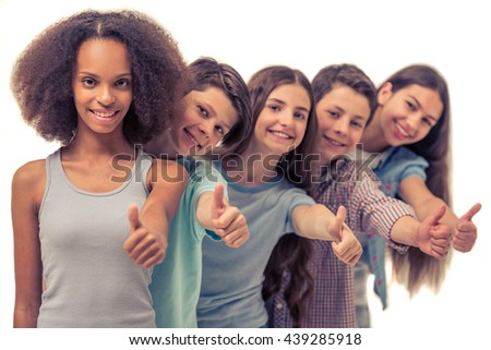 Group of teenage boys and girls is showing Ok sign, looking at camera and smiling, standing in row one by one, Afro American girl in the foreground - stock photo