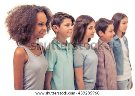 Group of teenage boys and girls is smiling while standing in row, isolated on white - stock photo