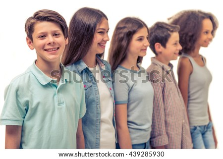 Group of teenage boys and girls is standing in row, isolated on white, boy in the foreground is looking at camera and smiling - stock photo