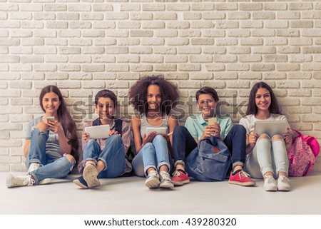 Group of teenage boys and girls is using gadgets, looking at camera and smiling, sitting against white brick wall - stock photo