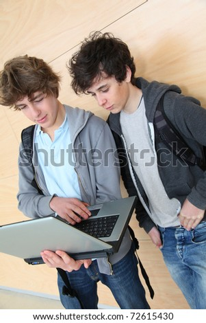 Group of teenage boys at school with laptop computer