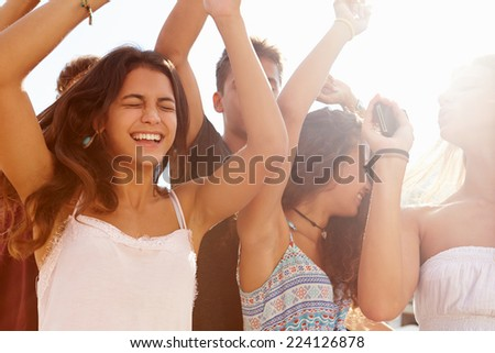 Group Of Teenage Friends Dancing Outdoors Against Sun - stock photo