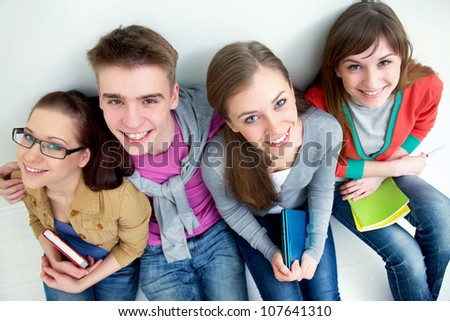 group of teenage friends look up at the camera with bright smiles - stock photo