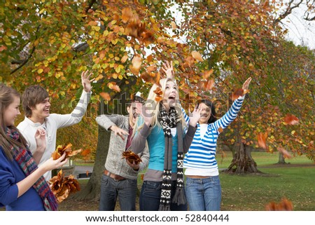 Group Of Teenage Friends Throwing Leaves In Autumn Landscape - stock photo