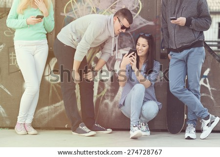 Group of teenage friends using their mobile phones in a skate park or schoolyard.