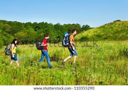 Group of teenage friends with backpacks hiking - stock photo