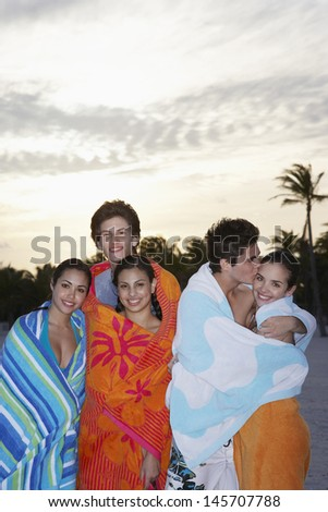 Group of teenage friends wrapped in towels at beach - stock photo