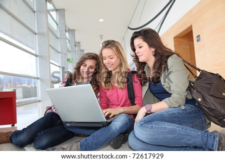 Group of teenage girls at school with laptop computer - stock photo