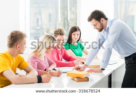 Group of teenage students studying at the lesson in the classroom - stock photo