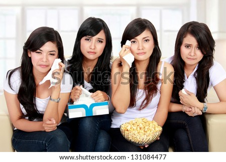Group of teenager girl sitting on couch watching movie with sad expressions