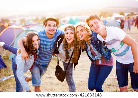Group of teenagers at summer music festival, sunny day - stock photo
