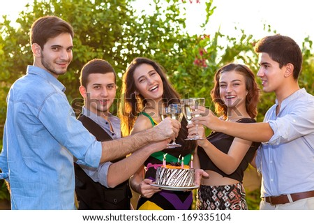 Group of teenagers celebrating a birthday laughing happily as they raises their glasses of champagne in a toast to the beautiful young girl holding a birthday cake with burning candles - stock photo
