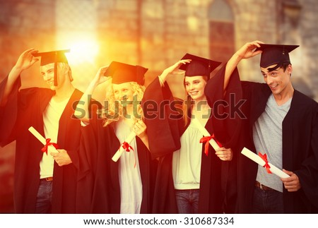 Group of teenagers celebrating after Graduation against grey school building - stock photo