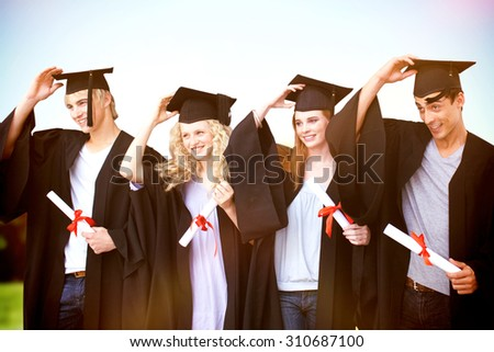 Group of teenagers celebrating after Graduation against sun rise over trees - stock photo