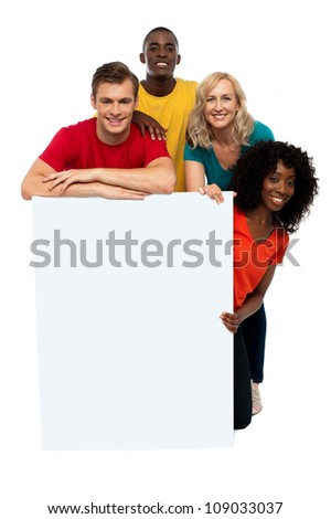 Group of teenagers displaying white banner in front of camera