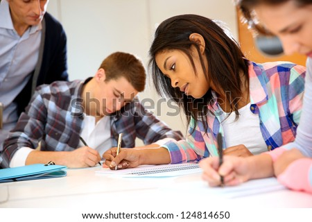 Group of teenagers in class writing an exam - stock photo