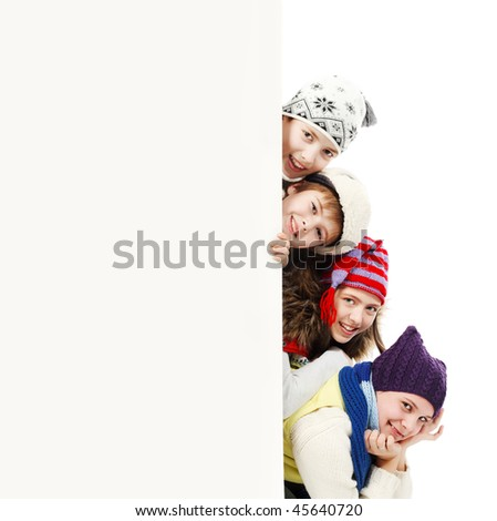 Group of teenagers in warm clothes looking out white board. - stock photo