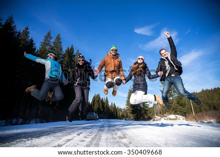Group of teenagers jumping together in wintertime. - stock photo