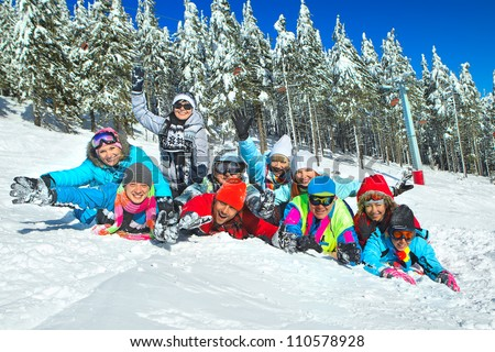 Group of teenagers laid on the snow in wintertime - stock photo