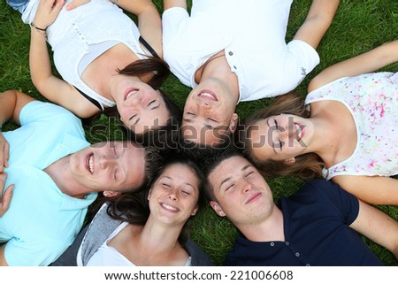 Group of teenagers lying in the grass