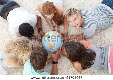 Group of teenagers lying on the floor examining a terrestrial world - stock photo