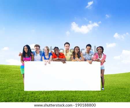 Group of teenagers posing with a white board on the hills.