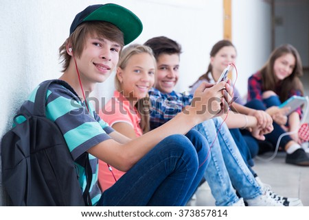group of teenagers sitting on the floor in the hallway  - stock photo