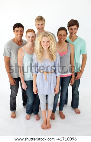 Group of teenagers standing and smiling in front of the camera - stock photo