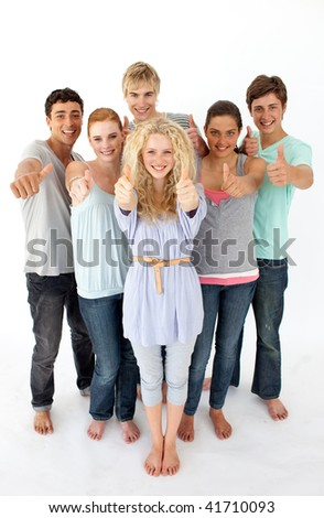 Group of teenagers standing and smiling in front of the camera with thumbs up