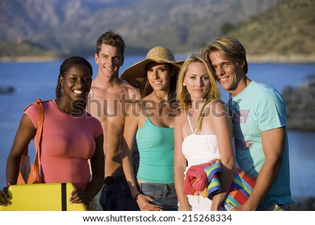 Group of teenagers standing near lake, smiling, portrait - stock photo