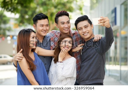 Group of teenagers taking selfie together outdoors - stock photo