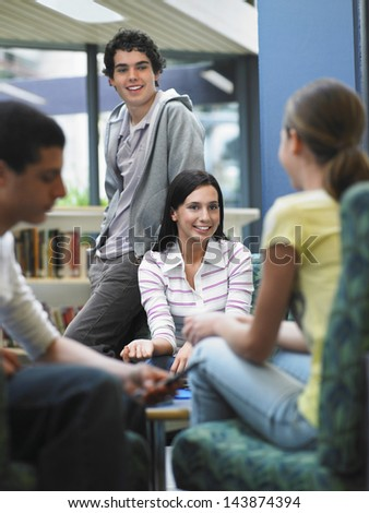 Group of teenagers talking in library - stock photo