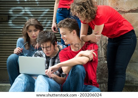 Group of teenagers with laptop computer outside - stock photo