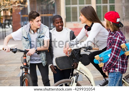 Group of teens chatting near bikes  in the town