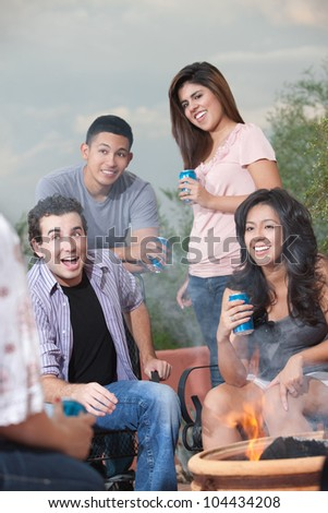 Group of teens hanging out at a barbecue drinking soda - stock photo