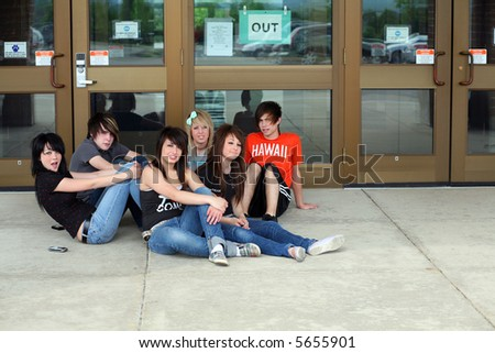 group of teens sitting outside school entrance - stock photo