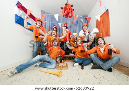 Group of ten cheering sports fans watching their national sports team at home - stock photo