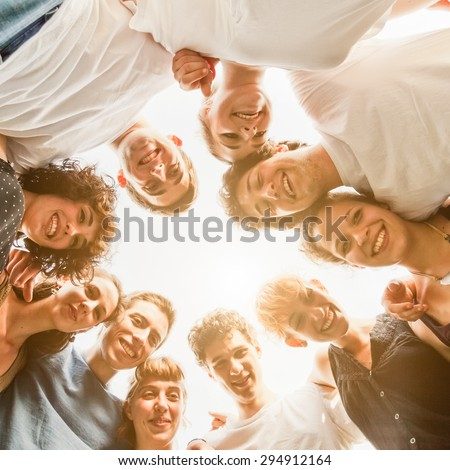 Group of ten young teenagers friends gathered to form a circle in the park, embraced each other. Group seen from bottom to top, during a summer day in a park at sunset - stock photo
