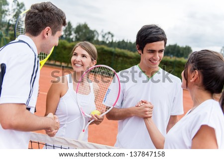 Group of tennis players giving a handshake after a match - stock photo