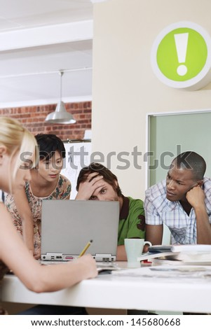 Group of tensed multiethnic business people using laptop in office - stock photo
