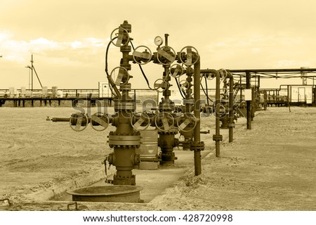 Group of the industrial wellheads and pipeline with valves. Oil and gas theme.