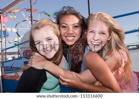 Group of three Asian and white teenage girlfriends at a carnival - stock photo
