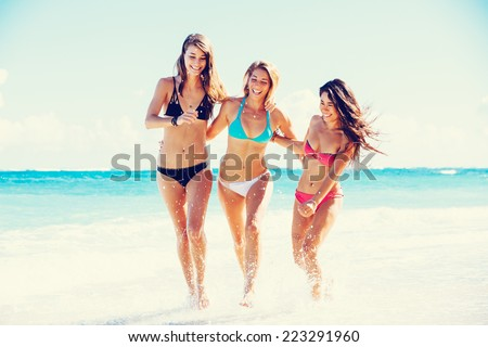 Group of Three Beautiful Attractive Young Women Walking on the Beach - stock photo