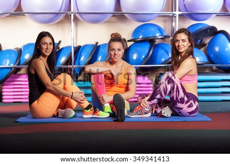group of three beautiful young women in gym are posing and smiling to the camera