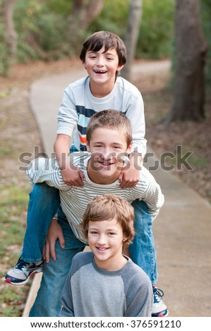 Group of three boys that are family and friends riding piggy back on sidewalk smiling at camera.