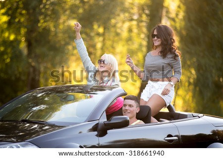 Group of three carefree smiling friends going on trip, traveling together in car on sunny summer day, girls having fun, rising hands, laughing
