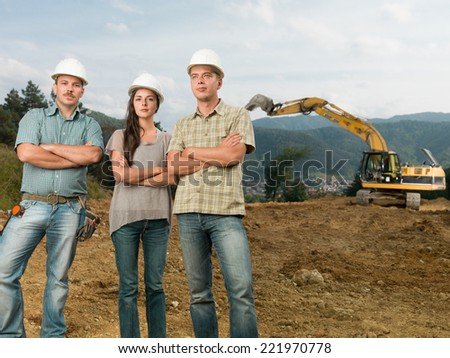 group of three caucasian architects standing with arms crossed on construction site outdoors - stock photo