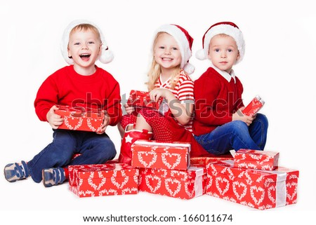 Group of three children in Christmas hat with presents over white background - stock photo