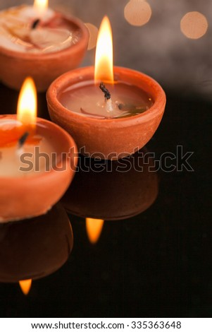 Group of three clay diyas with illumination and reflection. Indian celebration Diwali  with copy space - stock photo