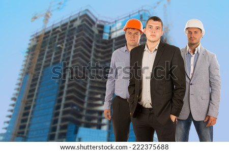 Group of three engineers and architects in their hardhats standing grouped in front of a skyscraper under construction on a building site in a teamwork and professional careers concept - stock photo